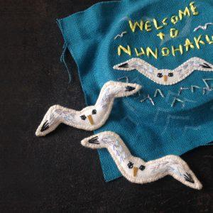 正面から迫ってくるカモメのブローチは笑われますが人気者です。(青い刺繍布は昨夏の立体マップです)