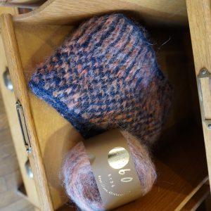 ストライプとチェックの編み込み柄がかわいいスヌードの編み物キット。(毛糸2玉+レシピ) ミックスカラーのシルクモヘア糸(オレシャプリンテット)が程よい色合いを生み出します。ひねって二重にして使うもよし、2つ折りにしてピンでとめてもよし。 表面を見せても、裏面を見せてもよしのマルチに使えるスヌードです。