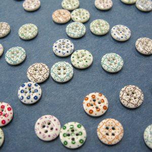 小花や幾何学模様が素朴でかわいいキャリコボタンのレプリカ。 11.5mmの小ボタンが63個も入ったお得なセットです。