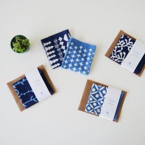 クラフト工房La Manoとつくった型染めの手ぬぐいです。東京都町田にある染織工房で障がいを持つ方々が制作をしています。藍は徳島産の本藍を使い、約100日かけて「すくも藍」をつくり、その染料を使って、1枚1枚丁寧に染めました。独特の風合いが魅力的です。