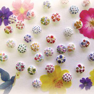 小花柄をプリントしたバリエーション豊かな小ボタンのシリーズ。 シャツボタンを一つだけ付け替えるのもさりげなくておしゃれです。