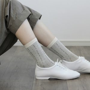 シャリ感のある綿麻クレープ糸で編立てた 薄地の靴下です。縦に流れるステッチは 雨垂れをイメージしてデザインしました。イエローとグレーの2色展開です。