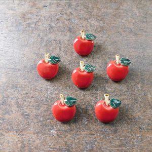 ぷっくりとした立体的な林檎のモチーフです。 定番の赤色以外にも、色んなカラーの林檎があります。