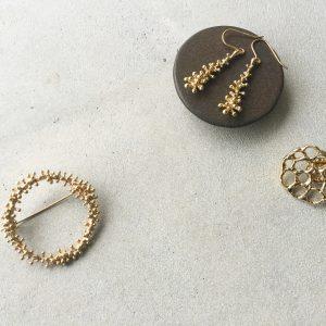 左から、ワイヤープランツのつぶつぶリースブローチ、こん棒ピアス、蓮の実ピンブローチ。どれも真鍮にK14コーティングを施しております。クリーミーな金色が特徴です。