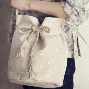 ラメ入りの帆布に白い糸でyozoraをイメージした刺繍を入れました。